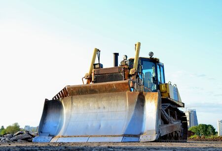 Track-type bulldozer on construction site. Land clearing, grading, pool excavation, utility trenching and foundation digging during of large construction jobs. Earth-moving equipment