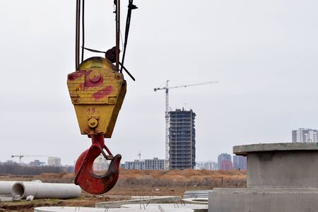 Large yellow-red crane hook on lifting fears and chains hanging on it for lifting loads on a background construction site, resedental building and jib crane