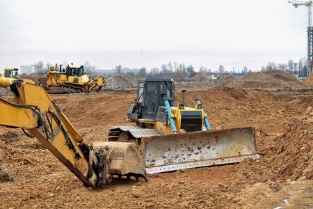 Excavator and a bulldozer work at a construction site. Land clearing, grading, pool excavation, utility trenching and foundation digging. Laying of underground storm sewer pipes.