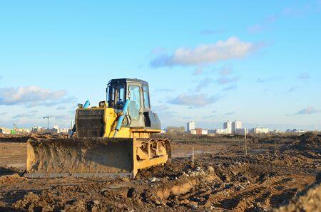 Bulldozer durante grandes trabajos de construcción en obra. Desbroce de tierras, nivelación, excavación de piscinas, excavación de zanjas de servicios públicos y excavación de cimientos. Tractor de orugas, topadora, equipo de movimiento de tierras. Foto de archivo