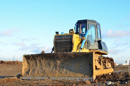 Bulldozer durante grandi lavori di costruzione in cantiere. Sgombero del terreno, livellamento, scavo di piscine, scavi di utilità e scavo di fondamenta. Trattore cingolato, apripista, attrezzatura per movimento terra.