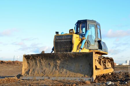 Bulldozer during of large construction jobs at building site. Land clearing, grading, pool excavation, utility trenching and foundation digging. Crawler tractor,  dozer, earth-moving equipment.