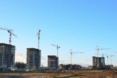 Tower cranes constructing a new residential building at a construction site against blue sky. Renovation program, development, concept of the buildings industry. Stock fotó
