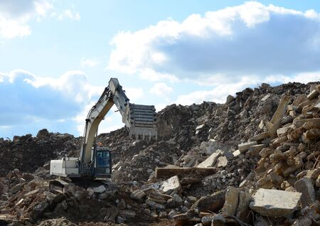 Salvaging and recycling building and construction materials. Industrial waste treatment plant. Excavator work at landfill with concrete demolition waste. Re-use concrete for new construction