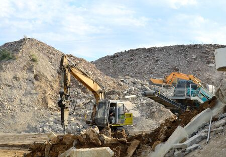 Salvaging and recycling building and construction materials. Excavator with hydraulic hammer work at landfill with concrete demolition waste. Reinforced concrete mobile shredder. Reuse concrete