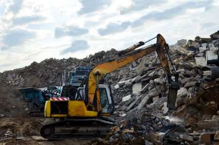 Salvaging and recycling building and construction materials. Excavator with hydraulic hammer work at landfill with concrete demolition waste. Reuse concrete for new construction