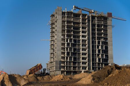 Dump truck dumps its load of sand and soil on construction site for road construction or for foundation work. Tower crane constructing a new residential building against blue sky. Industrial concept