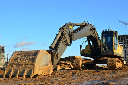 Excavator at a construction site on a background of a construction cranes and building. Backhoe dig the ground for the foundation, laying storm sewer pipes. Installation of water main systems.