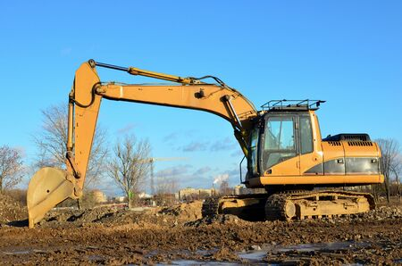 Tracked excavator working at a construction site during laying or replacement of underground storm sewer pipes. Installation of water main, sanitary sewer, storm drain systemsduring - Image Imagens