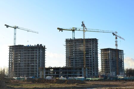 Tower cranes constructing a new residential building at a construction site against blue sky. Renovation program, development, concept of the buildings industry.