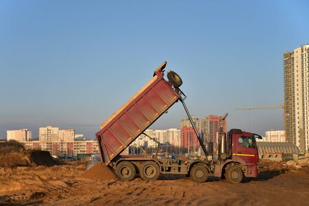 Red dump truck dumps its load of sand and soil on construction site for road construction or for foundation work. Transportation of bulk cargo.  Trucking industry, freight cargo transport Stock Photo