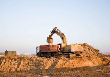 L'escavatore carica la sabbia sull'autocarro con cassone ribaltabile in cantiere. L'escavatore a cucchiaia scava il terreno per la fondazione e la costruzione di un nuovo edificio.