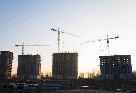 Tower cranes constructing a new residential building at a construction site against blue sky. Renovation program, development, concept of the buildings industry. Stock Photo