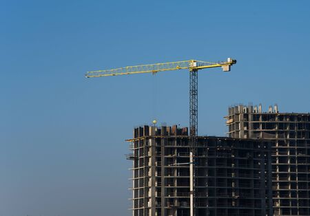 Tower crane constructing a new residential building at a construction site against blue sky. Renovation program, development, concept of the buildings industry. Stock Photo