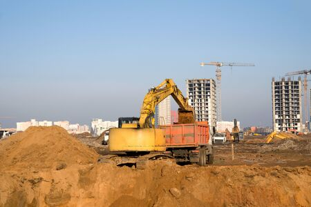 Excavator load the sand to the heavy dump truck on construction site. Excavators and dozers digs the ground for the foundation and construction of a new building. Apartment renovation program Stock Photo
