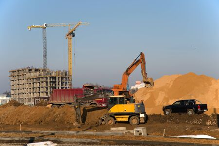 Excavator at a construction site on a background of a construction cranes and building. Backhoe dig the ground for the foundation, laying storm sewer pipes. Installation of water main systems. Stock Photo