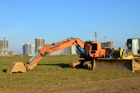 Crawler excavator with iron bucket and bulldozer at construction site. Land clearing, grading, pool excavation, utility trenching and foundation digging. Crawler tractor,  dozer, earth-moving equipment.