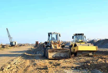 Soil Compactor and  wheel loader at construction site. Vibration single-cylinder road roller leveling the ground for the construct of the foundation for residential building, office, shopping center.