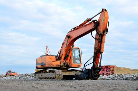 Crawler excavator with hydraulic hammer for the destruction of concrete and hard rock at the construction site. Replacing a concrete runway or road surface at an airport. Roadworks background - Image