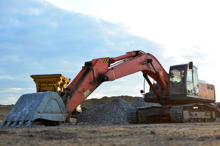 Large tracked excavator on a construction site. Road repair, asphalt replacement.  Loading of stone and rubble for its processing at a concrete factory into cement for construction work.