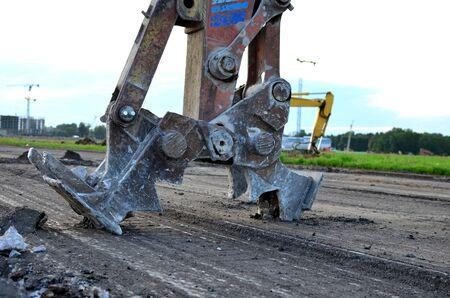 Bagger mit hydraulischer Schere bricht Asphalt auf einer Baustelle. Hydraulischer Scherenbrecher-Pulverisierer für Bagger. Robuster mechanischer Betonbrecher. Anbaugeräte Ausrüstung - Bild
