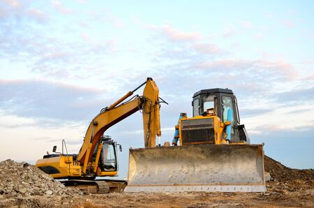 Track-type bulldozer, earth-moving equipment. Land clearing, grading, pool excavation, utility trenching, utility trenching and foundation digging during of large construction jobs. Stock Photo