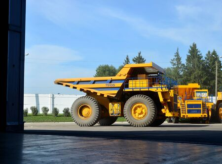 Heavy-duty trucks warehouse at autoworks. Giant mining dump trucks manufacture by the heavy vehicle plant. Heavy quarry equipment. Coal mining, granite, gravel, sand.