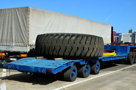 Transporting a large wheel for a mining truck on a truck trailer. The protector of a large rubber wheel. Rubber tire from the tipper  at an industrial plant for the production of cars. Banque d'images
