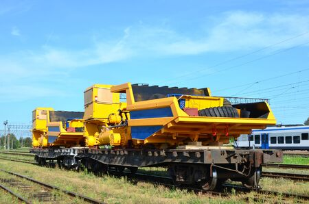 Logistics transportation heavy mining dump truck by rail. Yellow mining truck disassembled into parts, cab, body, electric motor, drive, wheels, loaded onto a cargo railway platform. Stock Photo