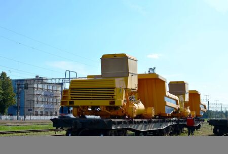 Logistics transportation heavy mining dump truck by rail. Yellow mining truck disassembled into parts, cab, body, electric motor, drive, wheels, loaded onto a cargo railway platform.