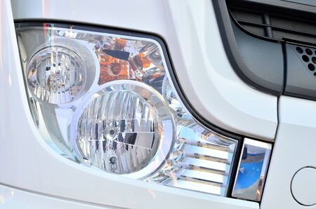 Frontal lighting products for on-highway vehicles, which includes integrated daytime running lights and beam patterns. Bi-Xenon and halogen headlamp of a modern truck, background texture - Image Imagens