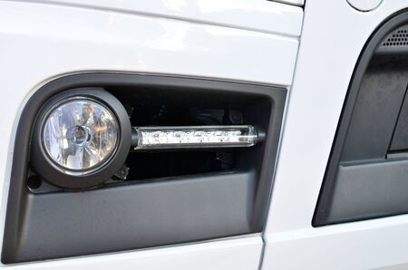Frontal lighting products for on-highway vehicles, which includes integrated daytime running lights and beam patterns. Bi-Xenon and halogen headlamp of a modern truck, background texture - Image Imagens - 137091876