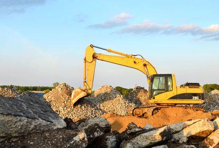 Une excavatrice lourde dans une carrière de granit décharge de vieilles pierres de béton pour le concassage et le recyclage en gravier ou en ciment. Équipement de construction lourd spécial pour la construction de routes.
