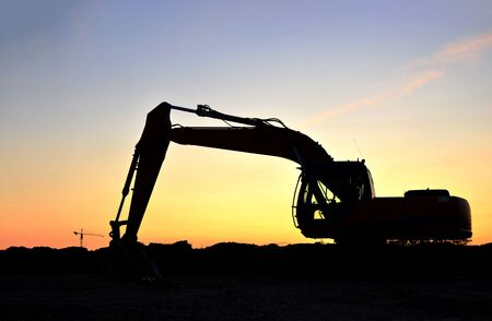 Silhouette of the heavy tracked excavator at a construction site on a background sunset. Special heavy construction equipment for road construction. Small roughness sharpness, possible granularity.