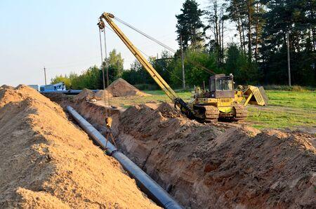 Lavori di costruzione di gasdotti. Una trincea scavata nel terreno per l'installazione e l'installazione di tubi industriali per gas e petrolio. Bulldozer con gru cingolata con braccio laterale o posatubi Archivio Fotografico