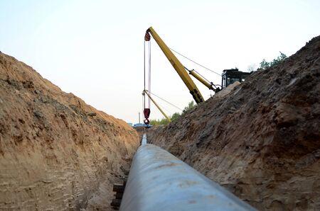 Lavori di costruzione di gasdotti. Una trincea scavata nel terreno per l'installazione e l'installazione di tubi industriali per gas e petrolio. Bulldozer con gru cingolata con braccio laterale o posatubi