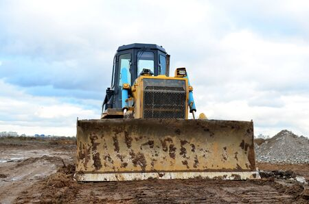Track-type bulldozer during of large construction jobs at building site. Land clearing, grading, pool excavation, utility trenching, utility trenching and foundation digging. Earth-moving equipment.