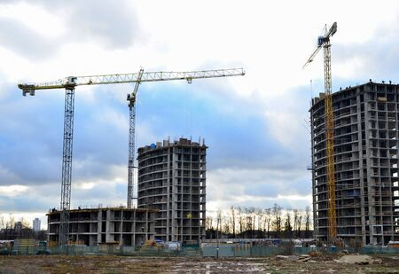 Tower cranes constructing a new residential building at a construction site against blue sky. Renovation program, development, concept of the buildings industry. Zdjęcie Seryjne