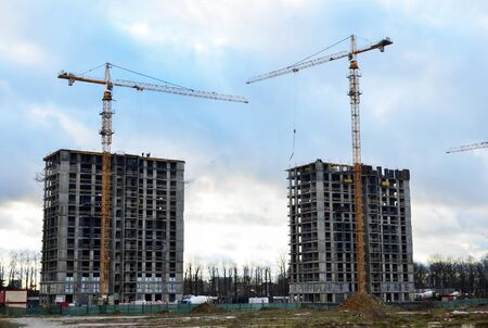 Tower cranes constructing a new residential building at a construction site against blue sky. Renovation program, development, concept of the buildings industry. 版權商用圖片