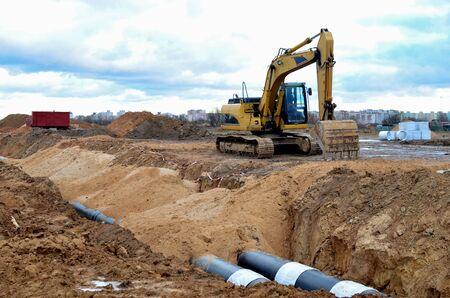 Escavatore cingolato che lavora in un cantiere edile durante la posa o la sostituzione di tubi fognari sotterranei. Installazione di rete idrica, fognatura sanitaria, sistemi di scarico temporalescodurante - Immagine Archivio Fotografico