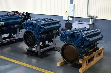 Large new diesel engines in the workshop of the factory for the production of trucks. Car's motor. Warning, small roughness sharpness, possible granularity.