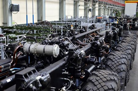 Industrial workshop for the production of trucks, wheel chassis and vehicles. Lightweight fixed frame air suspension, air springs and shock absorbers. Truck suspension and steering linkage. Stock Photo