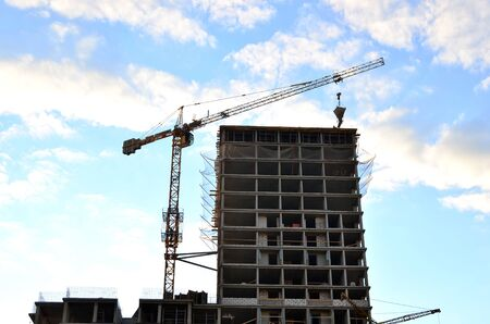 Tower cranes and new residential high-rise buildings at a huge construction site on background blue sky background. Building construction, installation of formwork and concrete structures - Image Stok Fotoğraf