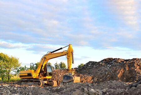 Gran excavadora de orugas trabaja en un pozo de grava. Carga de piedra y escombros para su transformación en una fábrica de hormigón en cemento para trabajos de construcción. Fábrica de producción de cemento en cantera minera