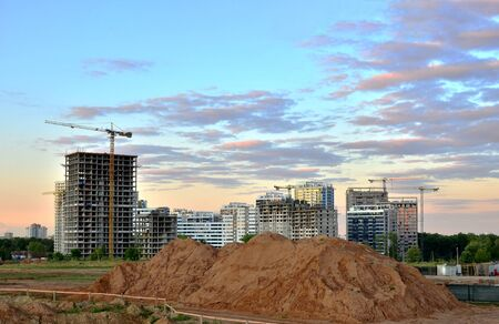 Tower cranes and new residential buildings at a huge construction site on the sunset and blue sky background - Image Stock fotó