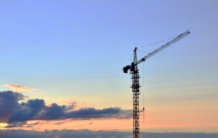 Grúa torre de construcción de pluma y nuevos edificios residenciales en un sitio de construcción en la puesta de sol y el fondo del cielo azul - Imagen