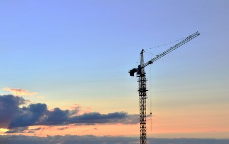 Jib construction tower crane and new residential buildings at a construction site on the sunset and blue sky background - Image