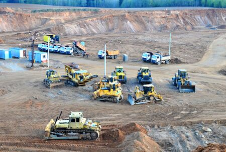 A lot of heavy construction equipment in the mining quarry. Parking with bulldozers, tractors, front loaders, excavators and dump trucks, top view - Image Stock Photo