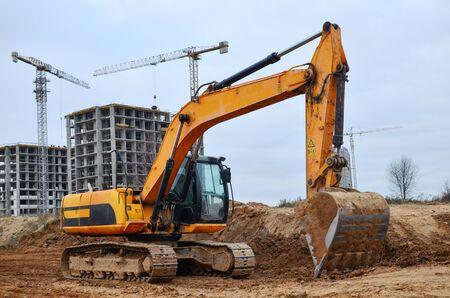 Bagger gräbt Boden auf einer Baustelle für die Installation von Betonsturmrohren. Baggern Sie den Graben der Pipeline. Kommerzielle und öffentliche Tiefbauarbeiten, Grabenaushub, Stampfen des Bodens Standard-Bild