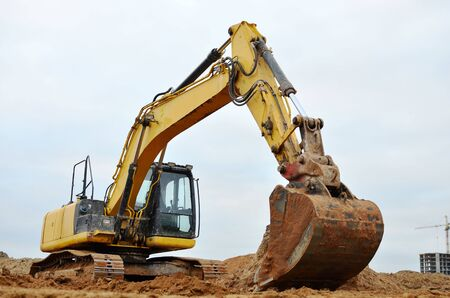 Excavadora excava el terreno para la fundación y construcción de un nuevo edificio. Reparación de carreteras, reemplazo de asfalto, renovación de una sección de una carretera, colocación o reemplazo de tuberías de alcantarillado subterráneas.